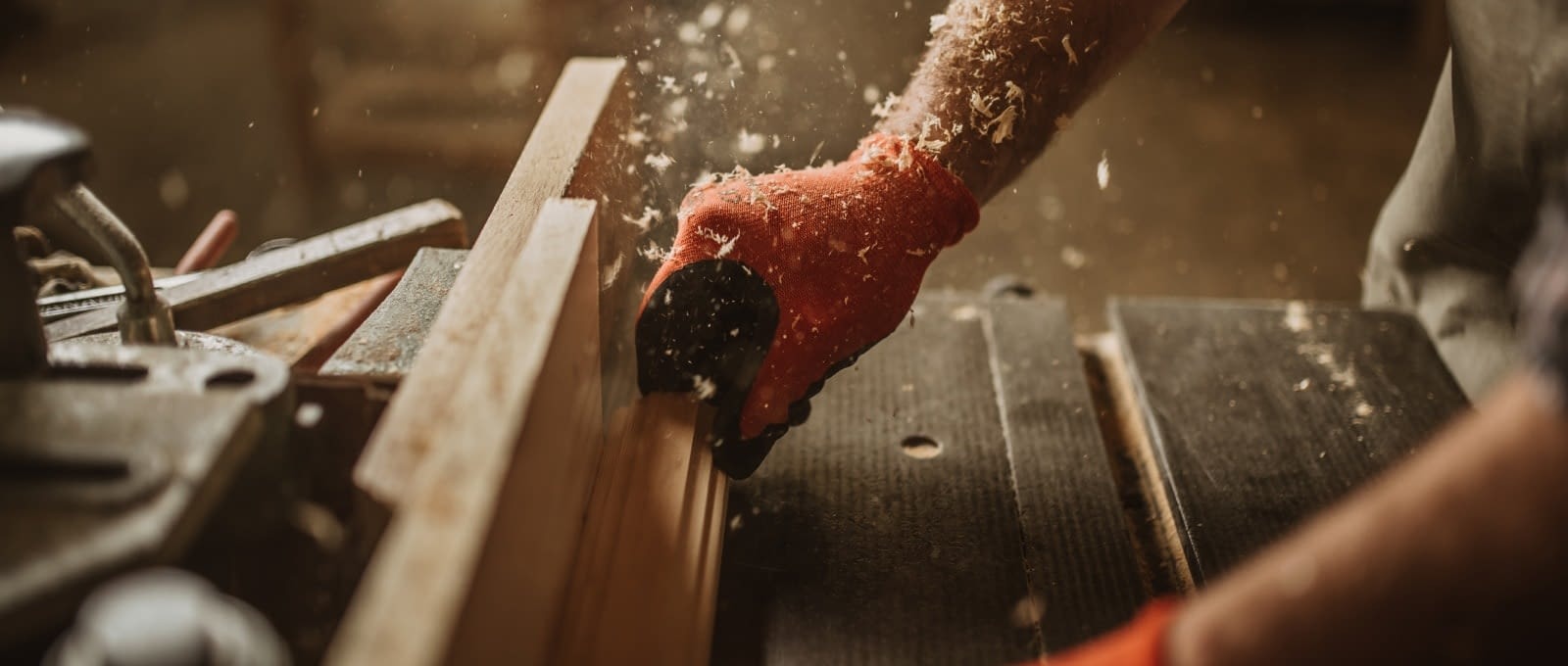 Woodworking - Close-up of a man pushing wood through a table saw